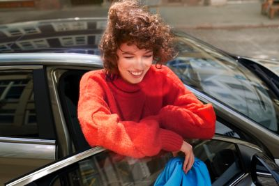 Woman in red sweater leaning on the doors of the new Hyundai i30.